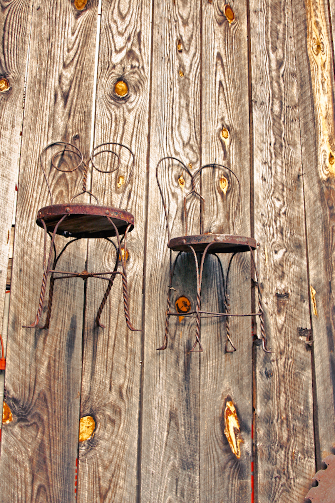 old-wrought-iron-chairs-hanging-on-barn-