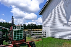 old-red-tractor-white-barn-blue-sky-980-2064